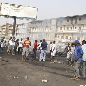 People gather at the site of a bomb explosion at a road in Kaduna, Nigeria (AP)