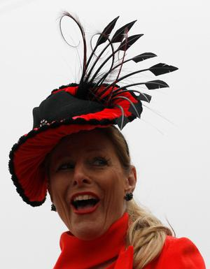 A woman poses in her hat on Ladies Day, the second day of racing at the Cheltenham Festival horse racing meet in Gloucestershire, western England March 14, 2012. REUTERS/Stefan Wermuth (BRITAIN - Tags: SPORT HORSE RACING ENTERTAINMENT)