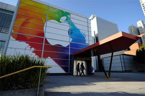 People walk past large Apple sign placed at the front entrance of the Yerba Buena Center for the Arts in preperation for the unveiling of the new iPad. Photo: Getty Images