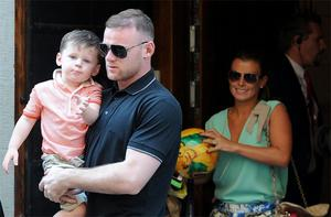 Wayne Rooney with his wife Coleen and son Kai, leaving the England team hotel in Krakow yesterday