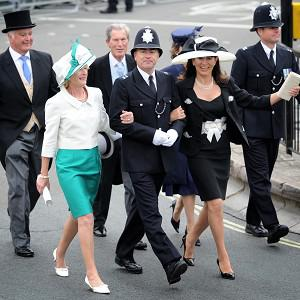A police officer escorts guests arriving at Westminster Abbey