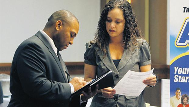Recruiter Esther Aranza, right, reviews job seeker Andrew Jack's CV at the National Career Fairs in Houston, Texas. The Department of Labor is scheduled to release initial and continuing jobless claims data on Thursday