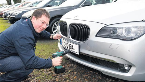 Raymond Quinn prepares new cars for sale at Adrian Quinn Car Sales in Labane, Co Galway