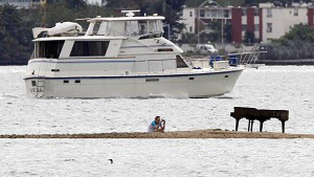 Freelance photographer Karla Murray takes a picture of a grand piano on a sandbar in Miami (AP)