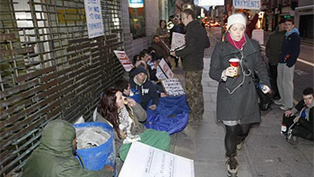 Members of #Occupydamestreet camp locked onto barrels of concrete outside the department of Finance