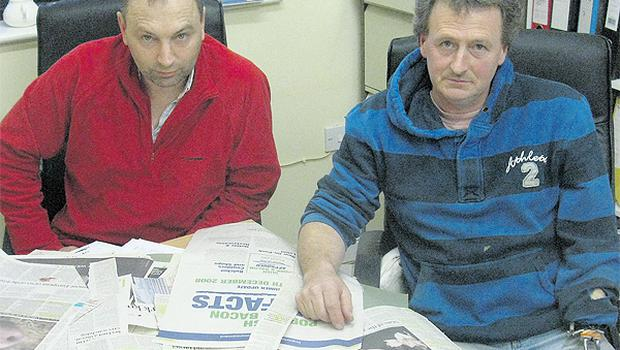 Robert Hogg, left, and Norman Bradley look at the scrapbook of press coverage from the pork dioxin incident