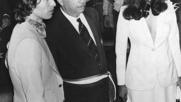 Marius Astezan, the Mayor of Saint-Tropez, stands between Rolling Stones singer Mick Jagger and his new bride Bianca Perez Morena de Macias during their wedding at Saint-Tropez Town Hall, 12th May 1971. The civil ceremony was followed by a religious one at the Chapel of St Anne. (Photo by Keystone/Hulton Archive/Getty Images)