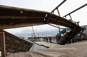MERRICK, NY - NOVEMBER 01: Framed by a mangled dock, workers at the Open Bay Marina make repairs in the aftermath of Superstorm Sandy on November 1, 2012 in Merrick, New York. Superstorm Sandy, which has left millions without power or water, continues to effect business and daily life throughout much of the eastern seaboard.  (Photo by Bruce Bennett/Getty Images)