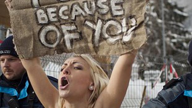 A topless Ukrainian protester from the campaign group Femen stage a demo outside the World Economic Forum in Davos (AP)