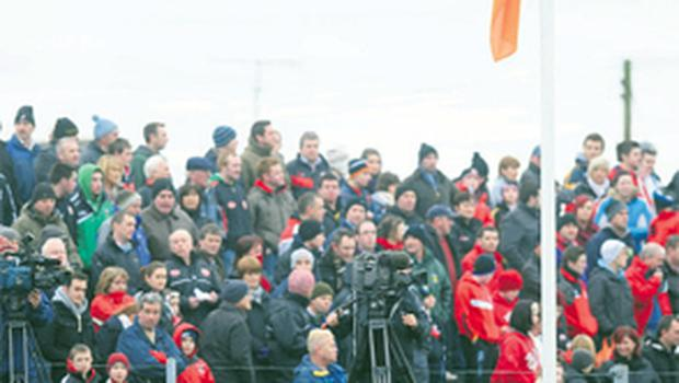 Mickey Harte watches the game from the sideline as the ground's flag is flown at half-mast