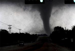 A tornado touches down in Lancaster, Texas south of Dallas. Tornadoes tore through the Dallas area Tuesday, peeling roofs off homes, tossing big-rig trucks into the air and leaving flattened tractor trailers strewn along highways and parking lots.