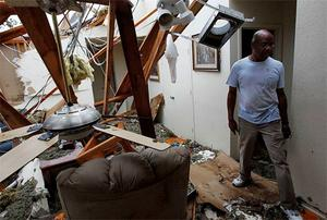 Lloyd Brown surveys the damage to his home after a tornado struck a residential neighborhood in Lancaster, Texas.