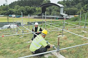 Workers put the finishing touches to the stage where Kings of Leon headline Saturday's bill