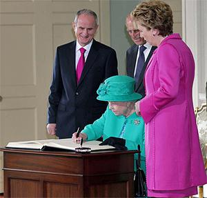 Queen Elizabeth II signs the visitors book watched by The Duke of Edinburgh, President Mary McAleese and Dr Martin McAleese at Aras An Uachtarain. Photo: PA