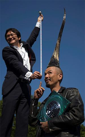 Television journalist Takashi Yanagisawa holds a measuring tape from atop a step ladder while interviewing Japanese fashion designer Kazuhiro Watanabe, who holds the world record for the tallest Mohawk