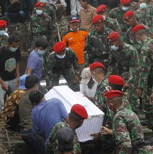 Indonesian soldiers carry the coffin bearing a victim of Mount Merapi eruption during a mass burial in Indonesia (AP)