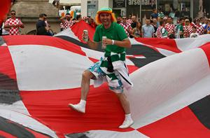An Irish supporter jumps over a large flag before the match