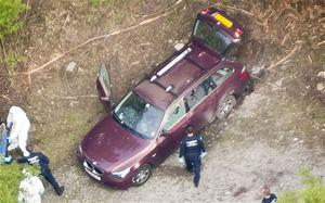 Police around the BMW at the scene of the shooting in woods near Chevaline in the French Alps