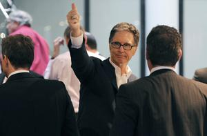 John W Henry, new owner of Liverpool Football Club, gestures to fans at the offices of Slaughter and May in London yesterday. Photo: Reuters.