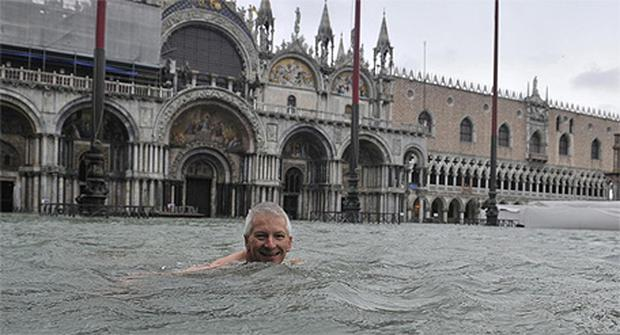 A man enjoys a swim in flooded St. Mark's Square in Venice