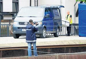 A coffin containing James Nolan's body is loaded into a coroner's van