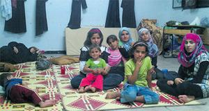 Girls pose for photos as others sleep at a temporary shelter at Houla, near Homs yesterday. Photo: Reuters