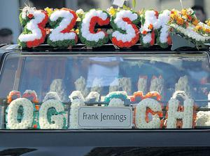 Red, white and green flowers from the 32 County Sovereignty Movement on the dead man's coffin