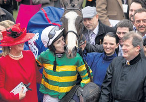 AP McCoy gives Synchronised a kiss after winning the Cheltenham Gold Cup yesterday, watched by JP McManus