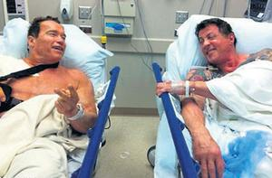the two action heroes pose for a picture in a Los Angeles hospital in February, where they were apparently to undergo treatment for shoulder injuries