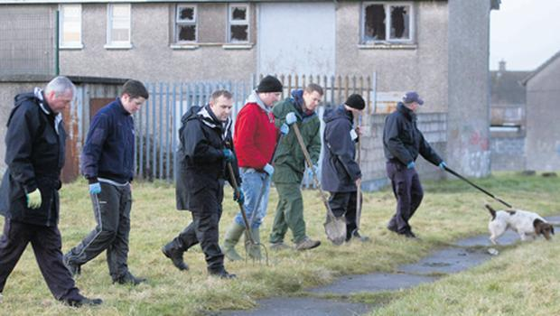 A garda search team combs nearby green areas for clues in O'Malley Park, Co Limerick, where the bodies were discovered