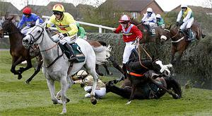 Neptune Collonges, grey, ridden by Daryl Jacob runs clear as members of the chasing pack struggle to clear the Aintree fences