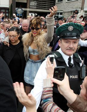 "Rihanna is mobbed by fans and members of the media during the second day of filming her new pop video in the new Lodge area of north Belfast. PRESS ASSOCIATION Photo. Picture date: Tuesday September 27, 2011. Rihanna got her marching orders after a farmer objected to her peeling off her clothes while filming a new video on his land, it was disclosed today. Alan Graham, 61, pulled up in his tractor and told the sexy singer to cover up and later claimed: ""Her behaviour was inappropriate."" See PA story SHOWBIZ Rihanna. Photo credit should read: Paul Faith/PA Wire"