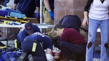 Emergency personnel attending to a shooting victim outside a shopping centre in Tucson, Arizona, on Saturday. Photo: AP