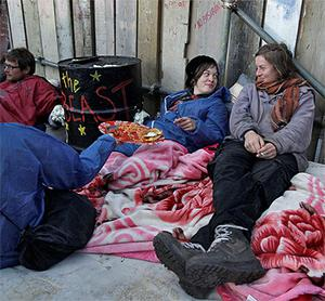 Activists sit next to a barrier at the entrance to the site