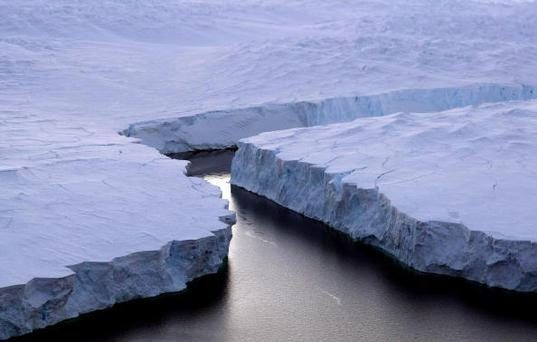 An enormous iceberg (R) breaks off the Knox Coast in the Australian Antarctic Territory on January 11, 2008. Australia's CSIRO's atmospheric research unit has found the world is warming faster than predicted by the United Nations' top climate change body, with harmful emissions exceeding worst-case estimates. AFP PHOTO/POOL/Torsten BLACKWOOD (Photo credit should read TORSTEN BLACKWOOD/AFP/Getty Images)