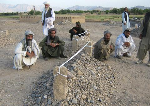 Villagers sit near the graves of victims of 'misdirected' US air strikes in the village of Garni in Afghanistan's Farah province. Photo: Getty Images