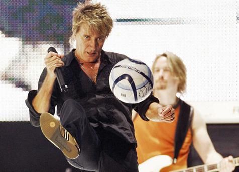 Rod Stewart kicks an autographed football into the audience at one of his concerts. Photo: Getty Images