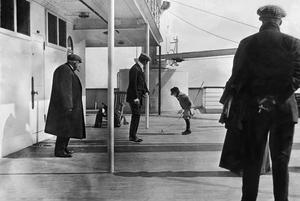 Robert Douglas Spedden, watched by his Father Frederic is playing on deck with a spinning top.