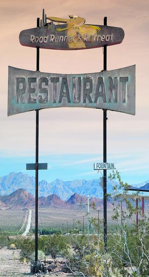Old restaurant sign at Route 66 near Chambless with Marble Mountains in distance.