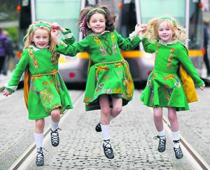 Eve Kirby (6), Erin Kirby (7) and Saoirse Kenny (6) encouraging people to attend the St Patrick's Day Festival ceili in Dublin on Friday.
