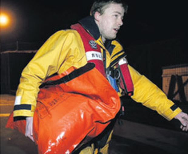RNLI crewman David Murphy arrives back at Dunmore East harbour last night with the survival kit from the 'Pere Charles'