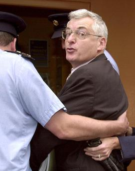 Going to jail: Socialist TD Joe Higgins being led into the Bridewell garda station yesterday after he was sentenced, with councillor Clare Daly, to one month in prison. Picture: Graham Hughes/Collins