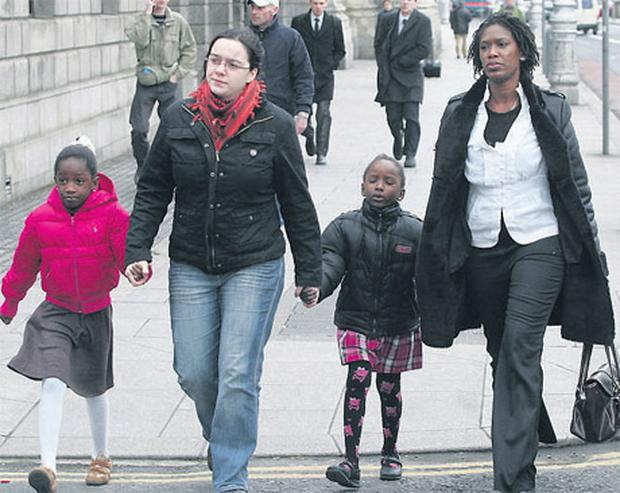 Pamela Izevbekhai (right), who faces deportation, leaving the High Court with her two children Naomi (7) and Jemima (5).