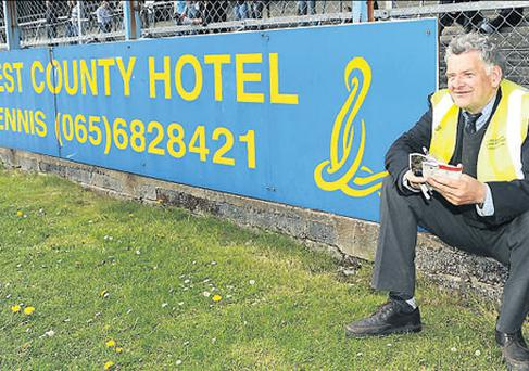 PJ O'Halloran, from Kilmurray in County Clare, watches yesterdays' Ladies National Football League Division 1 final at Cusack Park beside the sort of local advertisement hoarding that will be covered for championship matches