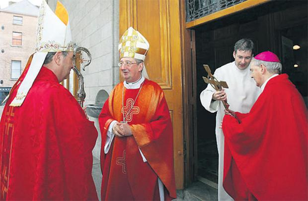 Ireland's new Papal Nuncio, Archbishop Giuseppe Leanza chats with Archbishop Diarmuid Martin as Bishop Dermot O'Mahony and Fr Damian McNeice prepare a crucifix for Archbishop Leanza to kiss before entering Dublin's Pro-Cathedral