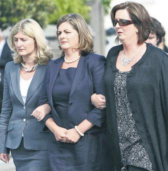 Arms entwined, the three daughters of social columnist Terry Keane struggled to fight back tears at her removal last night