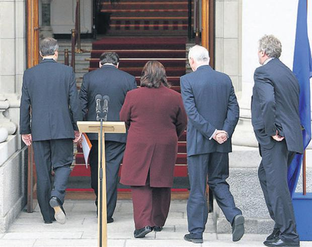 Taoiseach Brian Cowen leaves after speaking to the media at Government Buildings accompanied by Foreign Affairs Minister Micheal Martin, Health Minister Mary Harney, and Environment Minister John Gormley