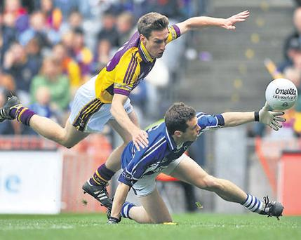 Wexford's Redmond Barry swarms all over Laois's Padraig McMahon during yesterday's Leinster SFC semi-final
