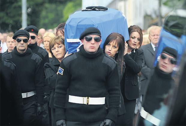 Christopher 'Crip' McWilliams was buried yesterday in a full-scale paramilitary funeral. His wife, Julie, (above right, with long hair and fringe) carried her husband's remains from requiem Mass in Newry.