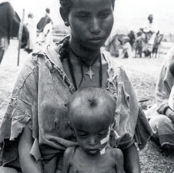 An Ethiopian child sits in his mother's lap at the Wad Sherife refugee camp in Sudan, near the Ethiopian border, in this image from March 13 1985. Much of what occurred in Ethiopia at this time was never reported in the Western media